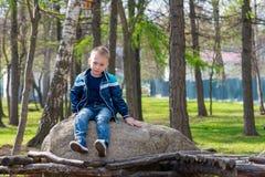 El muchacho que se sienta en la piedra Imagenes de archivo