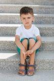 El muchacho que se sienta en las escaleras en el paso inferior Imagen de archivo libre de regalías