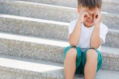 El muchacho que se sienta en las escaleras en el paso inferior Fotos de archivo libres de regalías