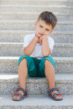 El muchacho que se sienta en las escaleras en el paso inferior Foto de archivo libre de regalías