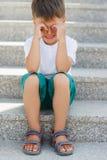 El muchacho que se sienta en las escaleras en el paso inferior Fotografía de archivo