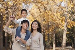 El muchacho que se sienta en sus padres lleva a hombros en un parque con la familia en otoño Fotos de archivo