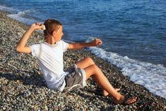 El muchacho que se sienta lanza la piedra en el mar Imagen de archivo libre de regalías
