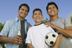 El muchacho (13-15) que sostiene el balón de fútbol con dos hermanos al aire libre afronta la opinión de ángulo bajo. Fotos de archivo