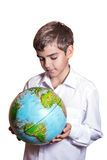 El muchacho que sostiene un globo, y lo examina de cerca Imágenes de archivo libres de regalías