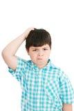El muchacho rasguña su cabeza en el puzzlement Fotos de archivo libres de regalías