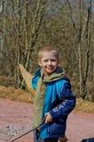 El muchacho recoge la leña en el bosque Imagen de archivo libre de regalías