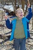 El muchacho recoge la leña en el bosque Fotografía de archivo