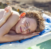 El muchacho Relaxed goza el mentir en un ocioso de la playa Fotografía de archivo