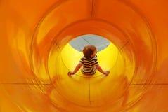 El muchacho resbala abajo en tubo Imagenes de archivo