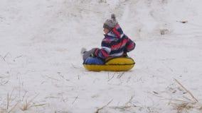 El muchacho resbala abajo la montaña en la nieve Imagen de archivo libre de regalías