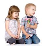 El muchacho resentido da a la muchacha una flor Aislado en la parte posterior del blanco Foto de archivo