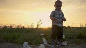 El muchacho rico lanza feliz una pila enorme de billetes de dólar en la tierra, cámara lenta almacen de metraje de vídeo
