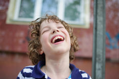 El muchacho rizado-cabelludo rubio ríe alegre Fotografía de archivo