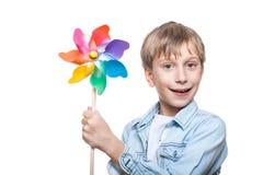 El muchacho rubio alegre hermoso que lleva la camisa elegante celebra una sonrisa colorida del molinillo de viento Foto de archivo libre de regalías
