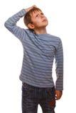 El muchacho rubio del niño en suéter rayado piensa el rasguño Foto de archivo libre de regalías