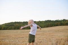 El muchacho rubio feliz se mantiene aparte con sus brazos y la cabeza para arriba en un campo de trigo segado Tiempo de la puesta fotografía de archivo