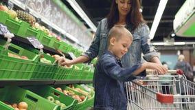 El muchacho rubio lindo está haciendo compras con su fruta de compra de la madre, él está tomando la manzana de la caja plástica  almacen de video