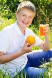 El muchacho rubio lindo se está sosteniendo de cristal con el zumo de naranja Fotografía de archivo
