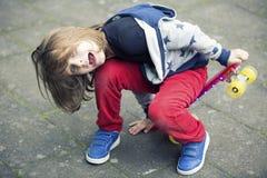 El muchacho rubio que se sienta en el monopatín y está riendo imagen de archivo libre de regalías