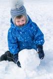 El muchacho rueda una bola de nieve Una bola de nieve para un muñeco de nieve Imagen de archivo libre de regalías
