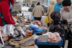 El muchacho ruso joven mira al vendedor de los pescados Foto de archivo