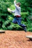El muchacho salta arriba en patio Fotografía de archivo