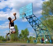 El muchacho salta con la bola del baloncesto Imagenes de archivo