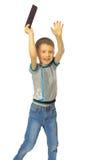 El muchacho salta con la tableta Imagen de archivo libre de regalías