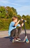El muchacho salta con la vespa en el parque del patín Imágenes de archivo libres de regalías