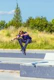 El muchacho salta con su vespa en un parque del patín Foto de archivo