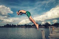 El muchacho salta en el agua Fotografía de archivo