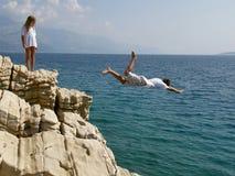 El muchacho salta en el mar Imagen de archivo libre de regalías