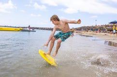 El muchacho salta en el océano con su tablero de la boogie Fotos de archivo