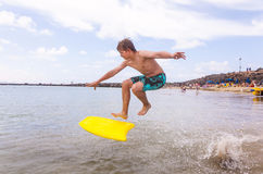 El muchacho salta en el océano con su tablero de la boogie Imágenes de archivo libres de regalías