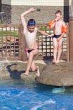 El muchacho salta en la piscina Fotografía de archivo