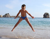 El muchacho salta en la playa fotografía de archivo
