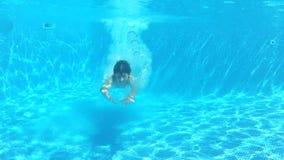 El muchacho salta en piscina después nada bajo el agua a la cámara almacen de video