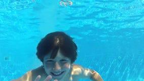 El muchacho salta en piscina después nada bajo el agua a la cámara almacen de metraje de vídeo