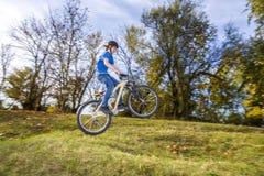El muchacho salta sobre una rampa con su bici de la suciedad Imagen de archivo libre de regalías