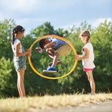 El muchacho salta a través de aro del hula Foto de archivo libre de regalías