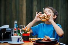 El muchacho sano lindo del adolescente come la hamburguesa y la patata Foto de archivo libre de regalías