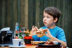El muchacho sano lindo del adolescente come la hamburguesa y la patata Imagenes de archivo