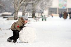 El muchacho sculpts el muñeco de nieve Foto de archivo libre de regalías