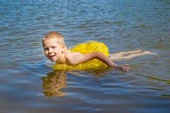 El muchacho se baña en el río Imágenes de archivo libres de regalías