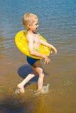 El muchacho se baña en el río Fotografía de archivo