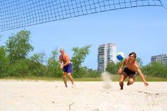 El muchacho se cae en la arena después de bola Foto de archivo