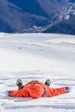 El muchacho se cayó abajo sobre nieve fresca Muchacho feliz que pone en nieve en su b Fotografía de archivo