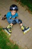 El muchacho se cayó los pcteres de ruedas Imágenes de archivo libres de regalías