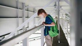 El muchacho se coloca bajo el puente y mirada en el agua Paseo debajo del puente Paisaje industrial metrajes